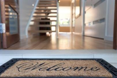 welcome mat in front of open door to hoe