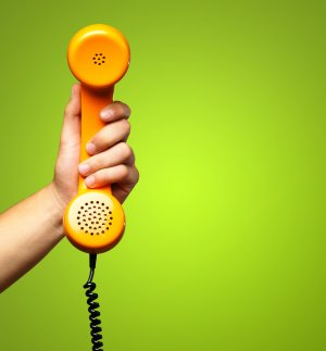 hand holding a corded orange phone against lime green background