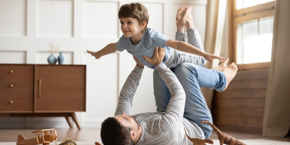 father and son playing together at home
