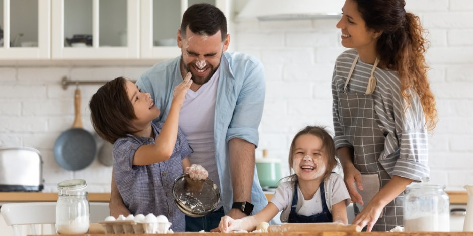 family of four in kitchen at home baking together
