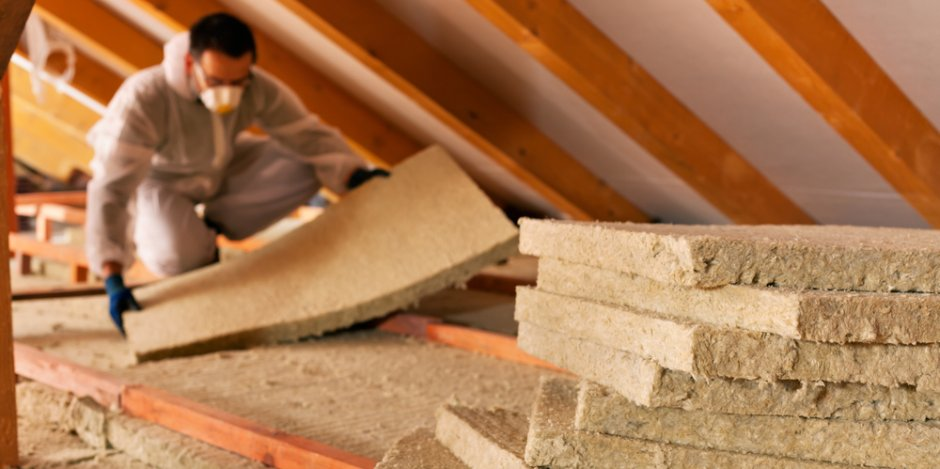 new insulation being installed in attic of home