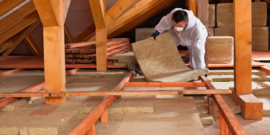 technician installing insulation in attic
