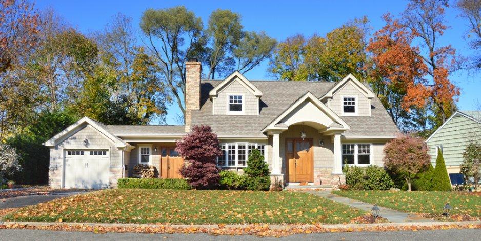 suburban house against autumn trees and blue skies